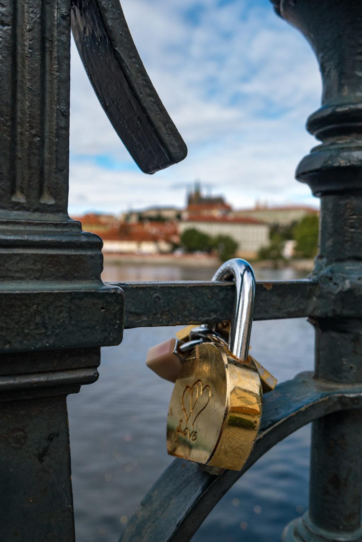 Love locks on a rail in Prague In the background, defoccused is Prague Castle