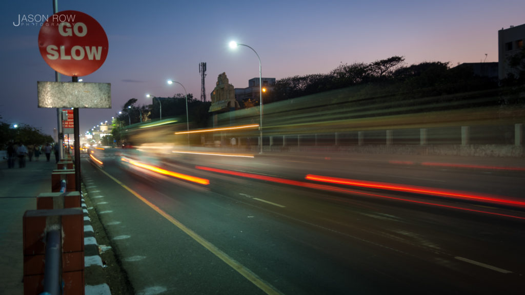 Cars speed past a Go Slow sign in Chennai