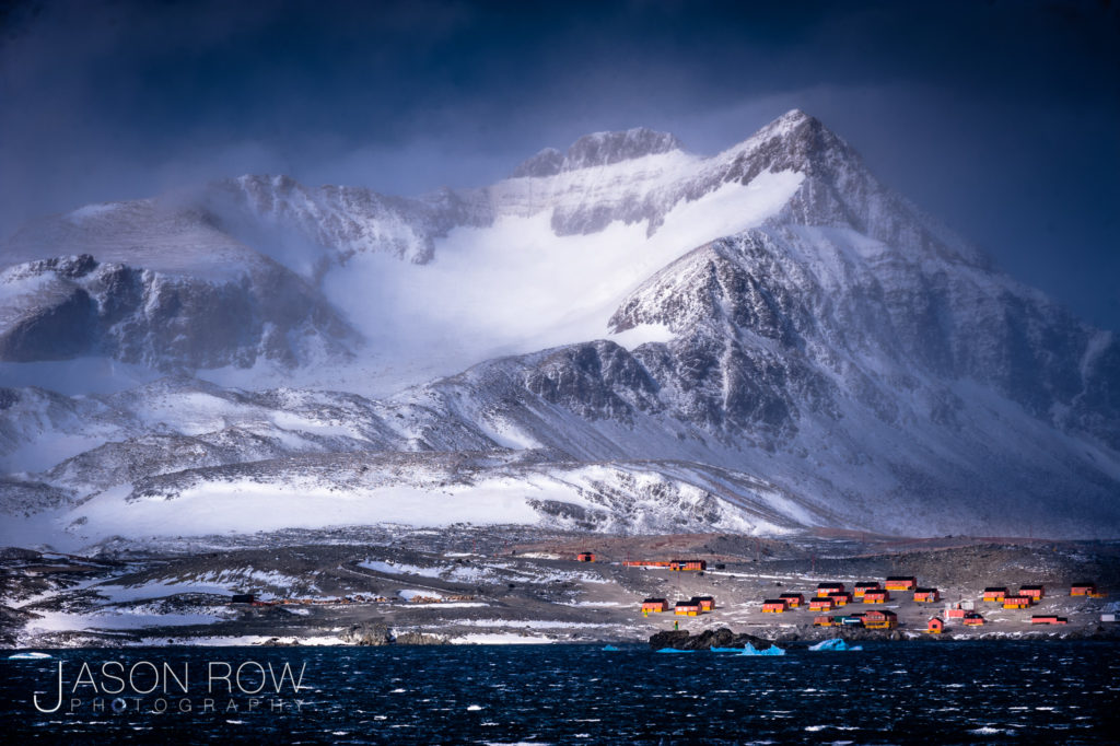 A stormy mountainous scene at the tip of the Antarctic peninsular. An Antarctic research base is seen at the foot of the mountain