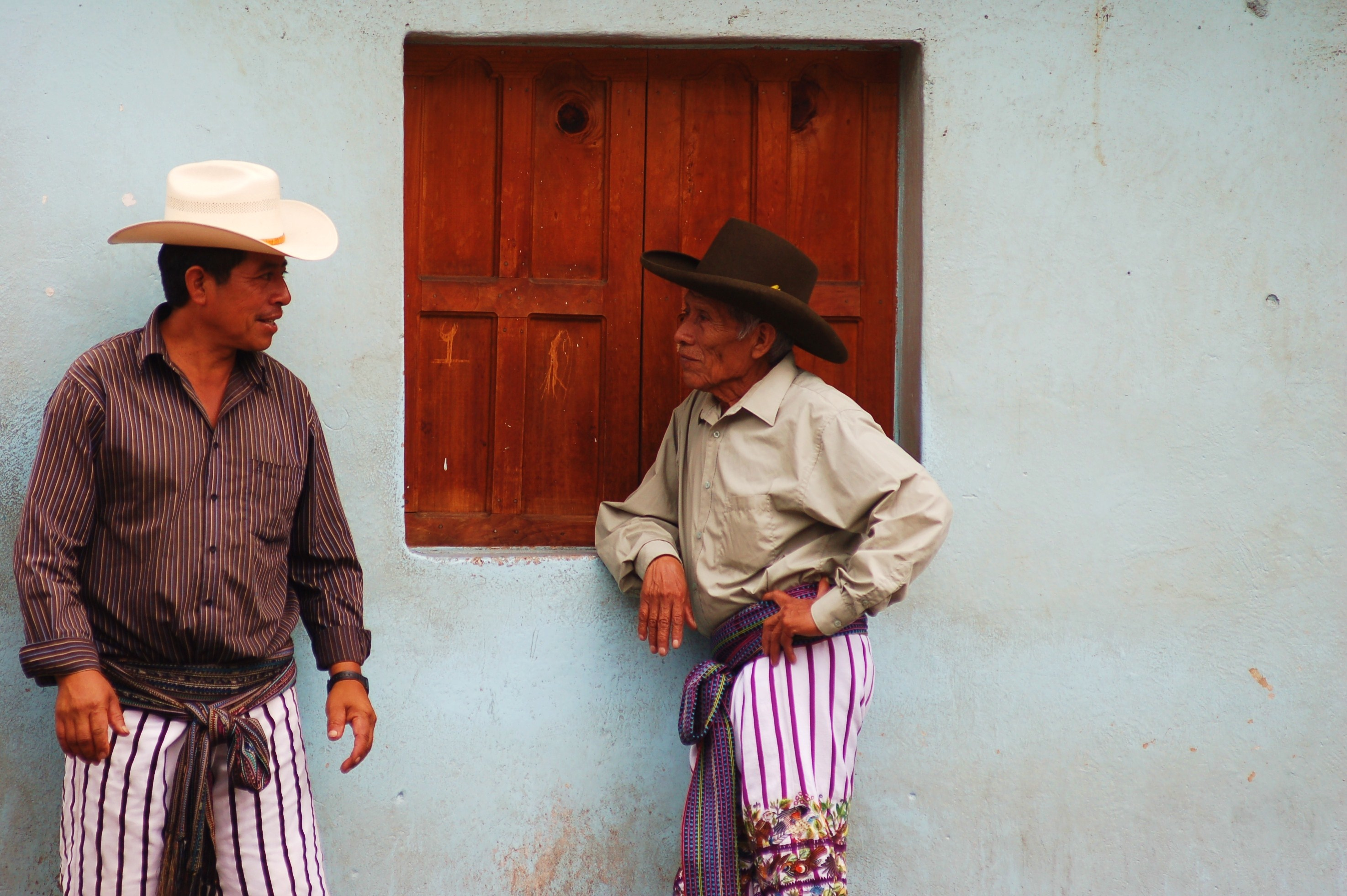 Men conversing at a market on Lake Atitlan.