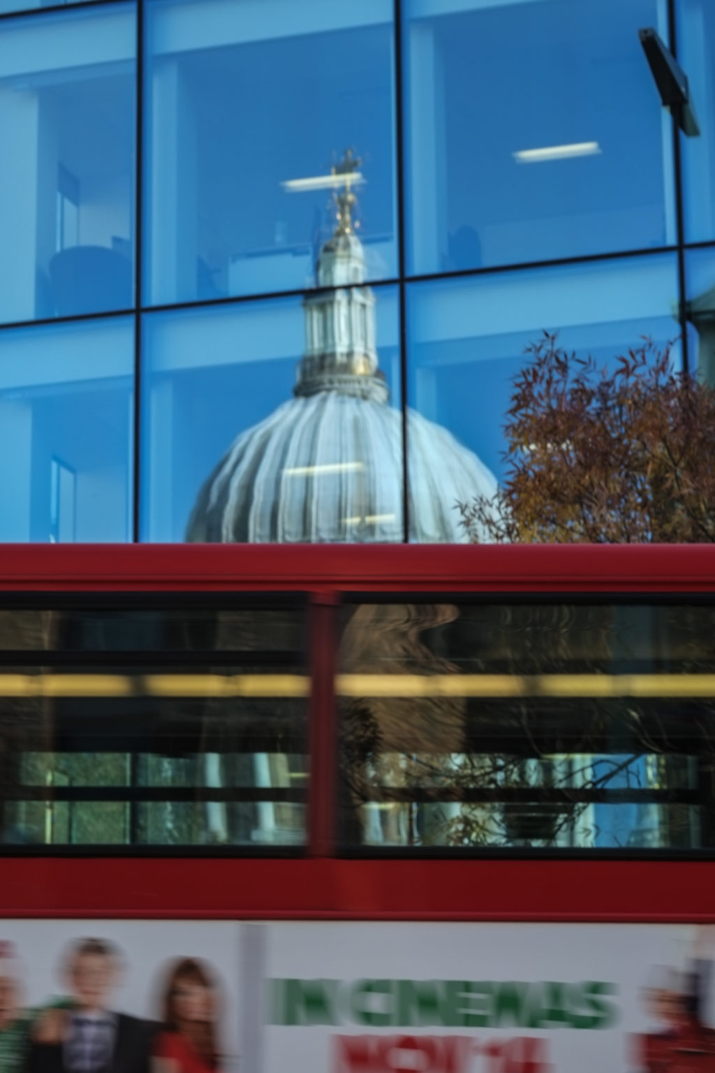 Red London bus passes reflection of St Pauls in modern office block.