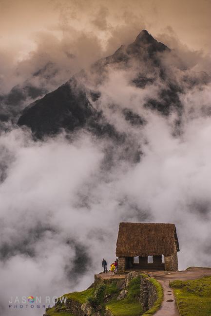 Clouds rise around and over the gatekeepers hut in Machu Picchu, Peru. The Peruvian highlands rise in the background