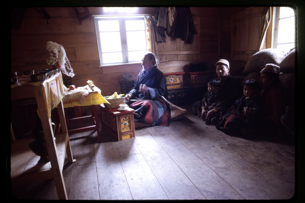 Family of sick girl with Poh, a shaman, during a religious ritual to heal the child