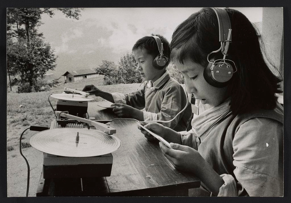 "Photograph shows children seated at table outdoors, using ""teaching machines"" (record players and headphones), Sikkim."