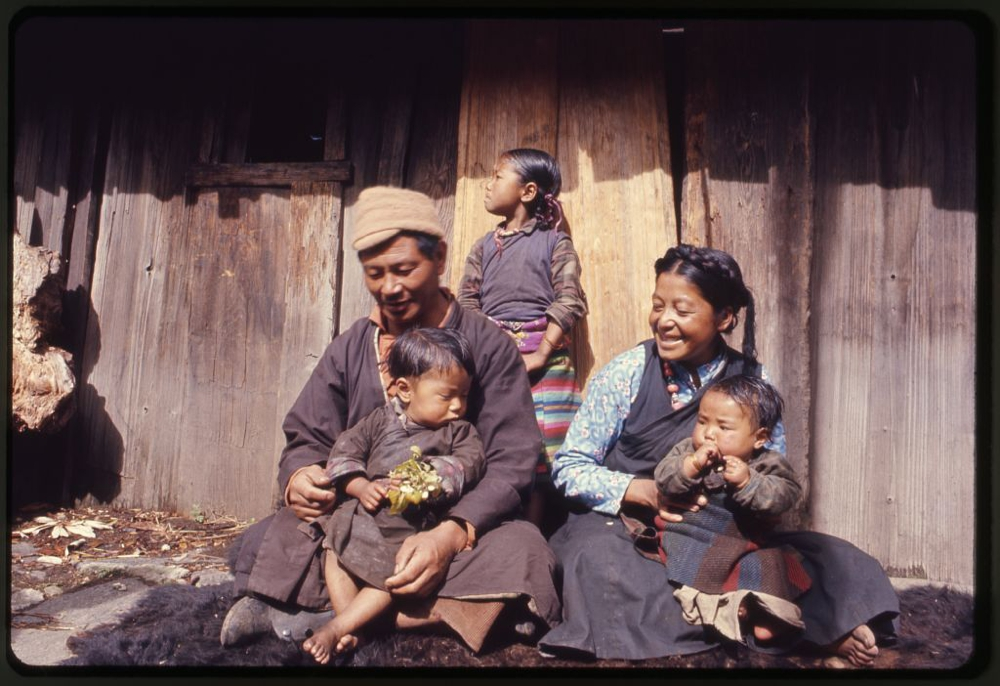 Photograph shows the mother, father and children of the Jorbu family, seated outside their home, Lachung, Sikkim