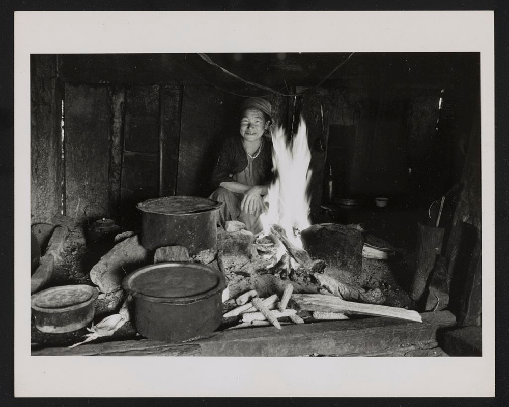 Kiranti woman cooking at the hearth in her house, Sikkim