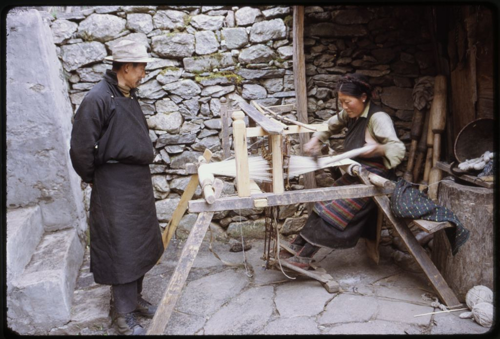 Photograph shows woman weaving on loom outdoors as a man watches, Lachung, Sikkim