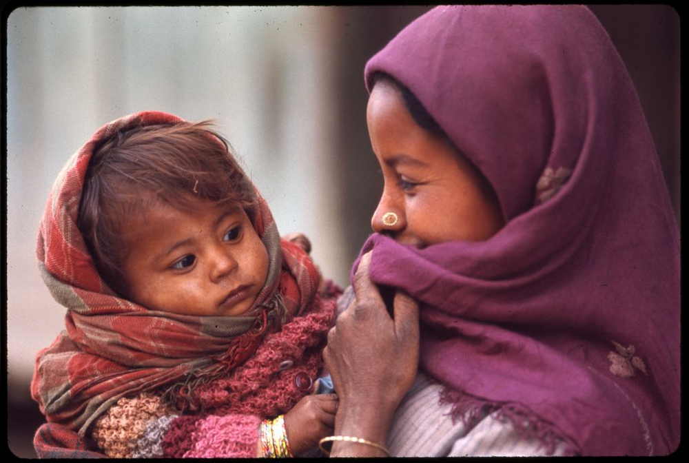 Nepalese woman wearing purple headscarf and nose ring, holding baby, Sikkim