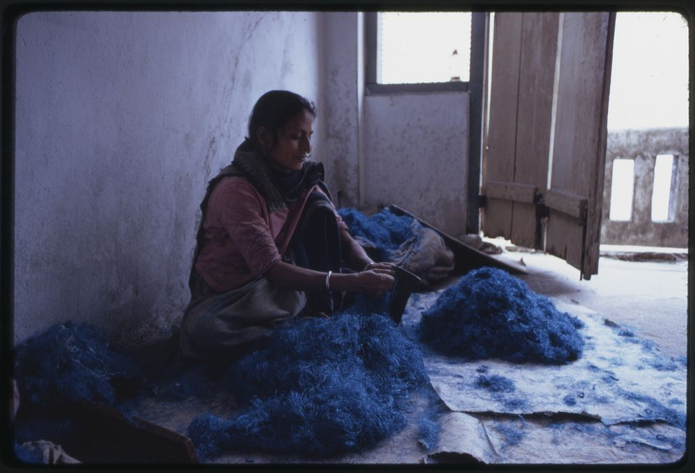 Nepalese woman working with blue dyed wool, Sikkim