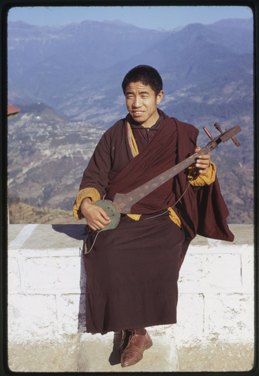Photograph shows a monk, seated on a wall, playing a lute, Rumtek, Sikkim.