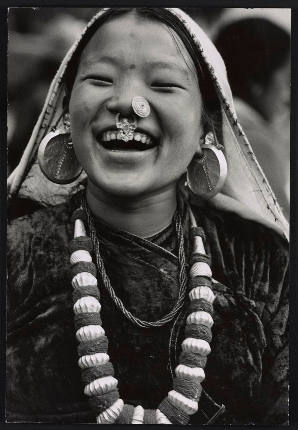 Photograph shows a Nepalese girl, head-and-shoulders portrait, facing front, smiling, wearing necklace, earrings and nose ornaments, in Sikkim.