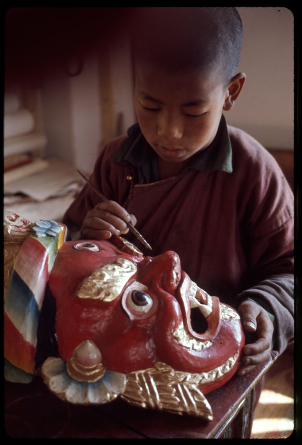 Sikkimese boy painting a mask