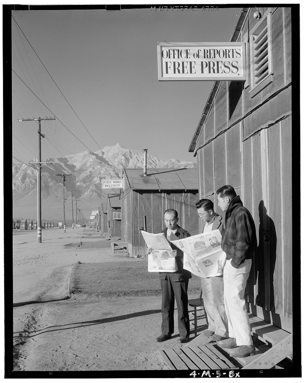 Roy Takeno (Editor) and group reading Manzanar paper [i.e. Los Angeles Times] in front of office, Yuichi Hirata, Nabuo Samamura, Manzanar Relocation Center, California