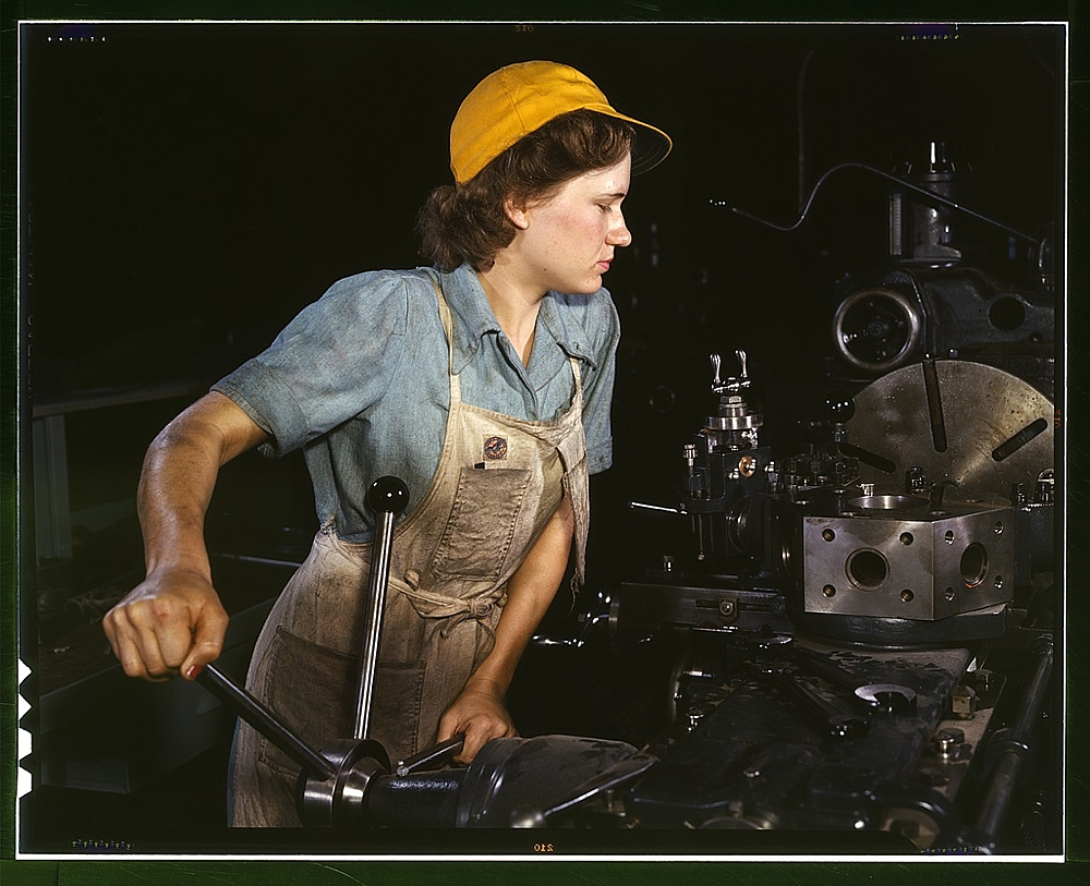 Lathe operator machining parts for transport planes at the Consolidated Aircraft Corporation plant