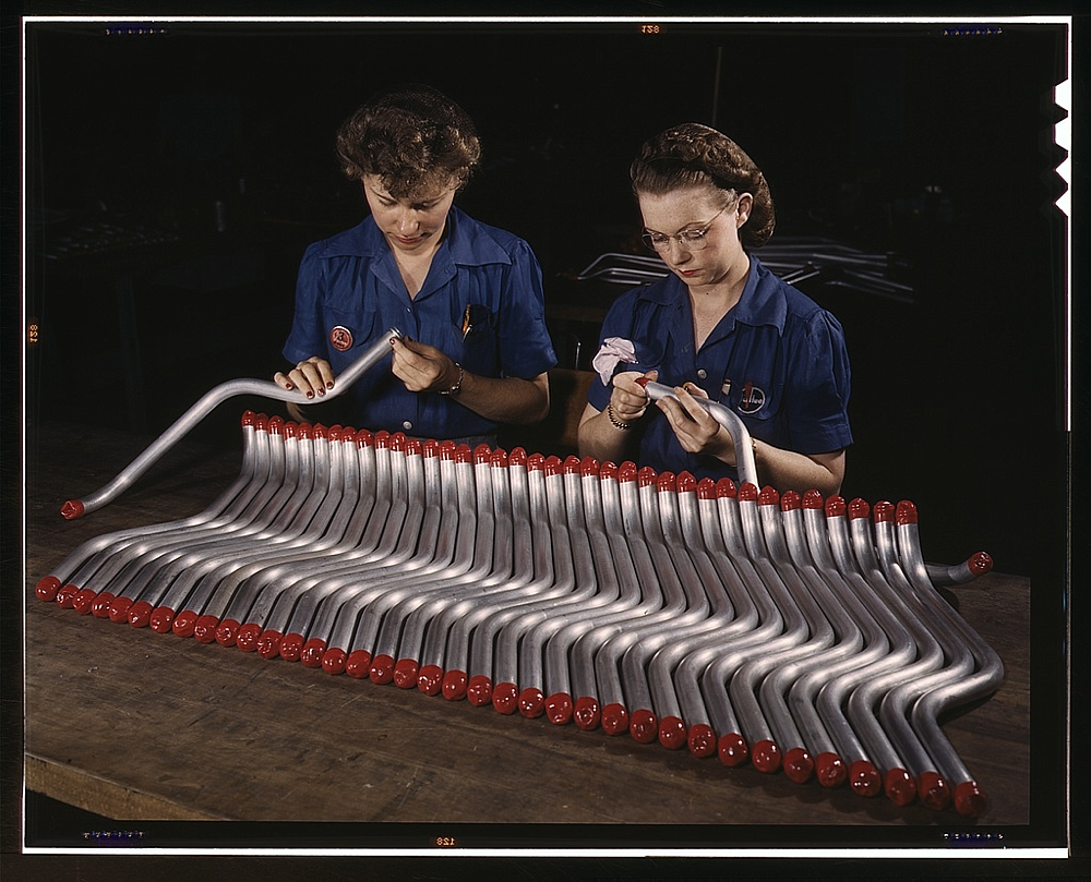 Two women workers are shown capping and inspecting tubing