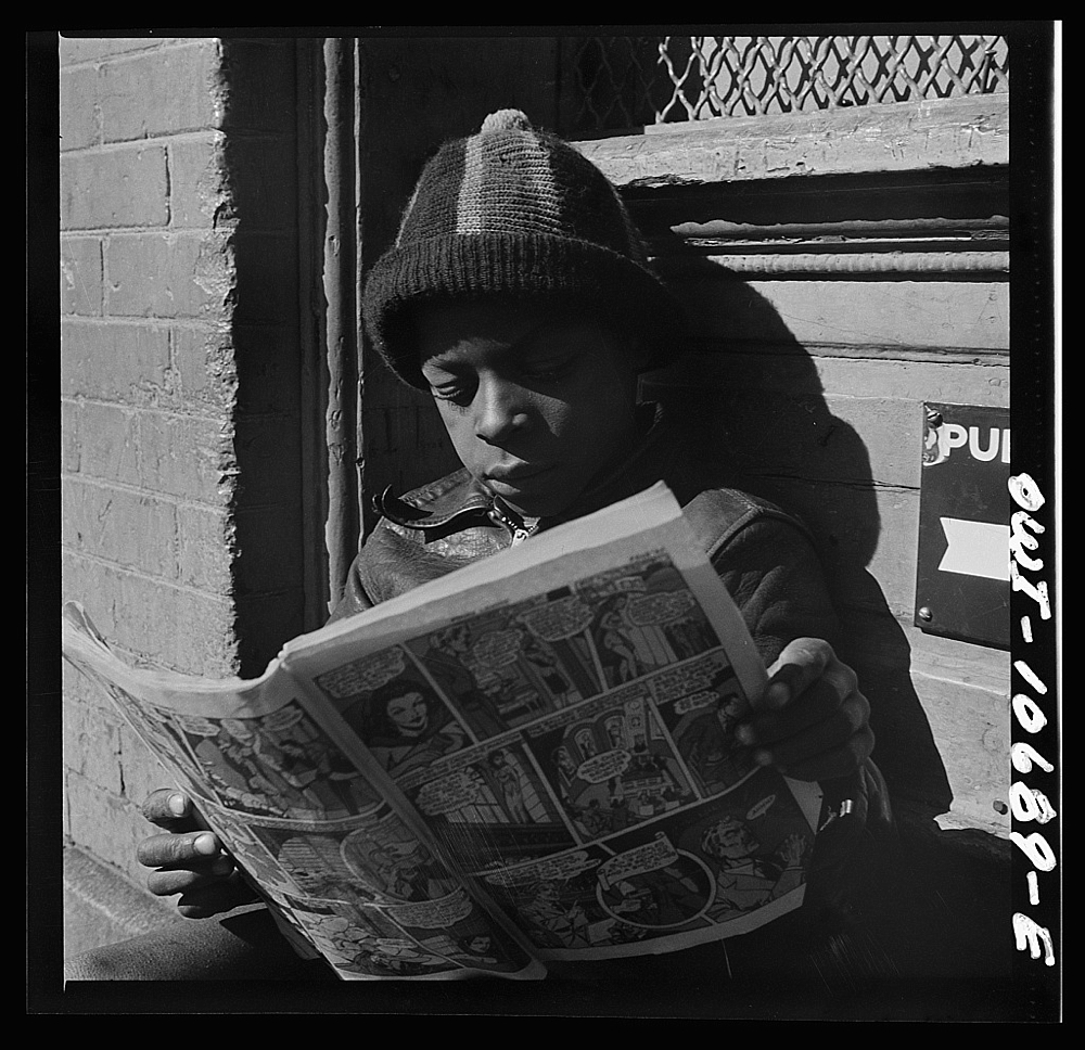 Washington, D.C. Negro youth reading a funny paper on a door step