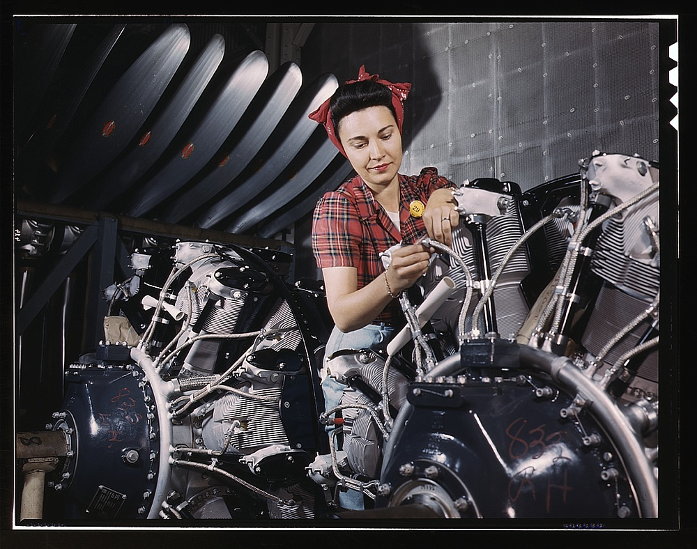Woman working on an airplane motor at North American Aviation