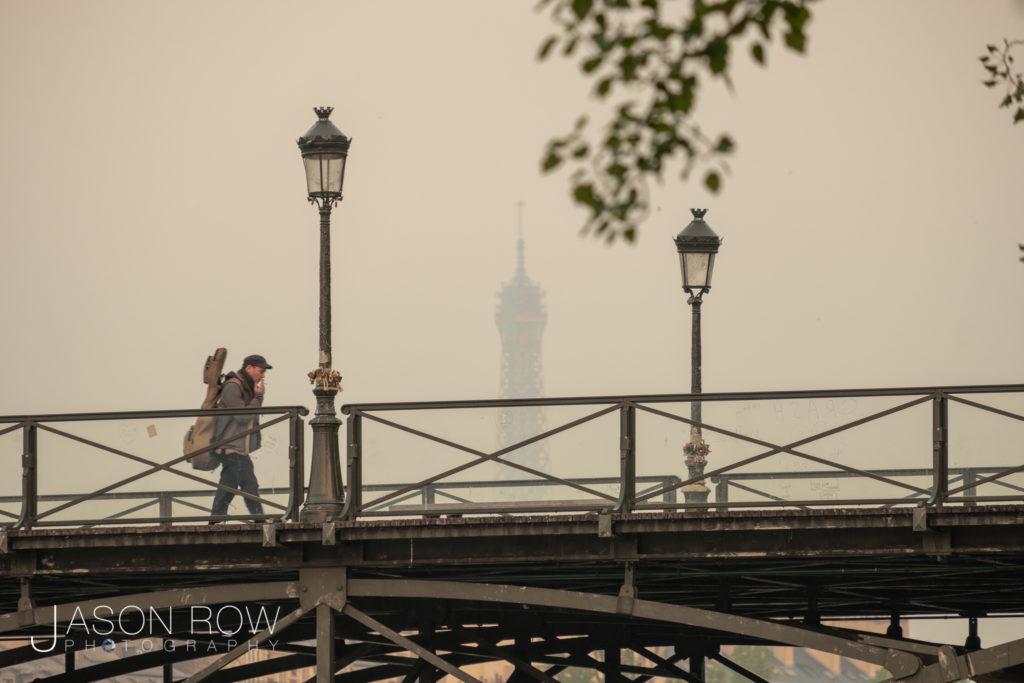 Long shot of man walking across the Pont des Art Paris towards t