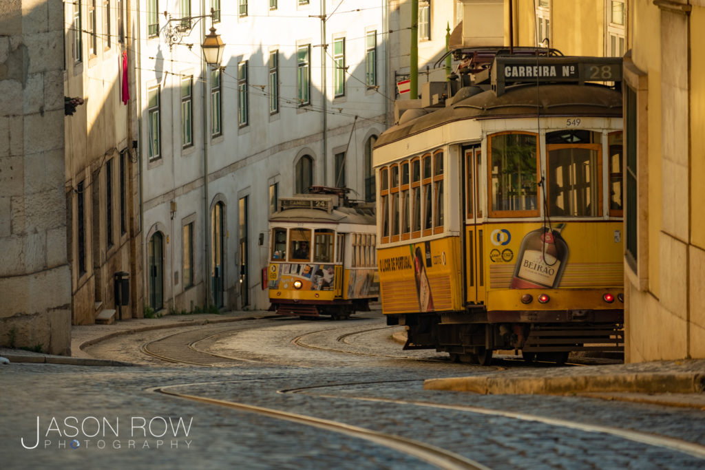 Telephoto clip of yellow old style tram line 28 climbing a hill in Lisbon, Portugal at dawn