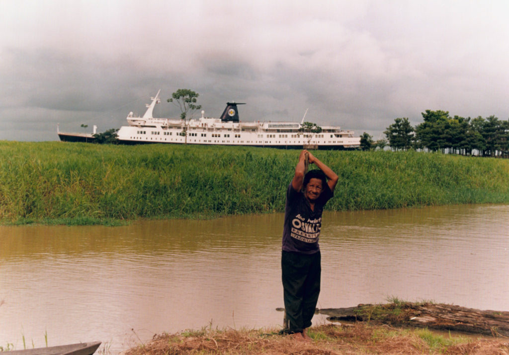Amazonian man stands by Amazon river with ship in background