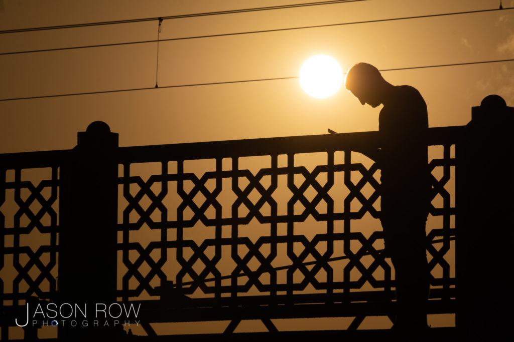 Silhouette of man on Galata Bridge at sunset