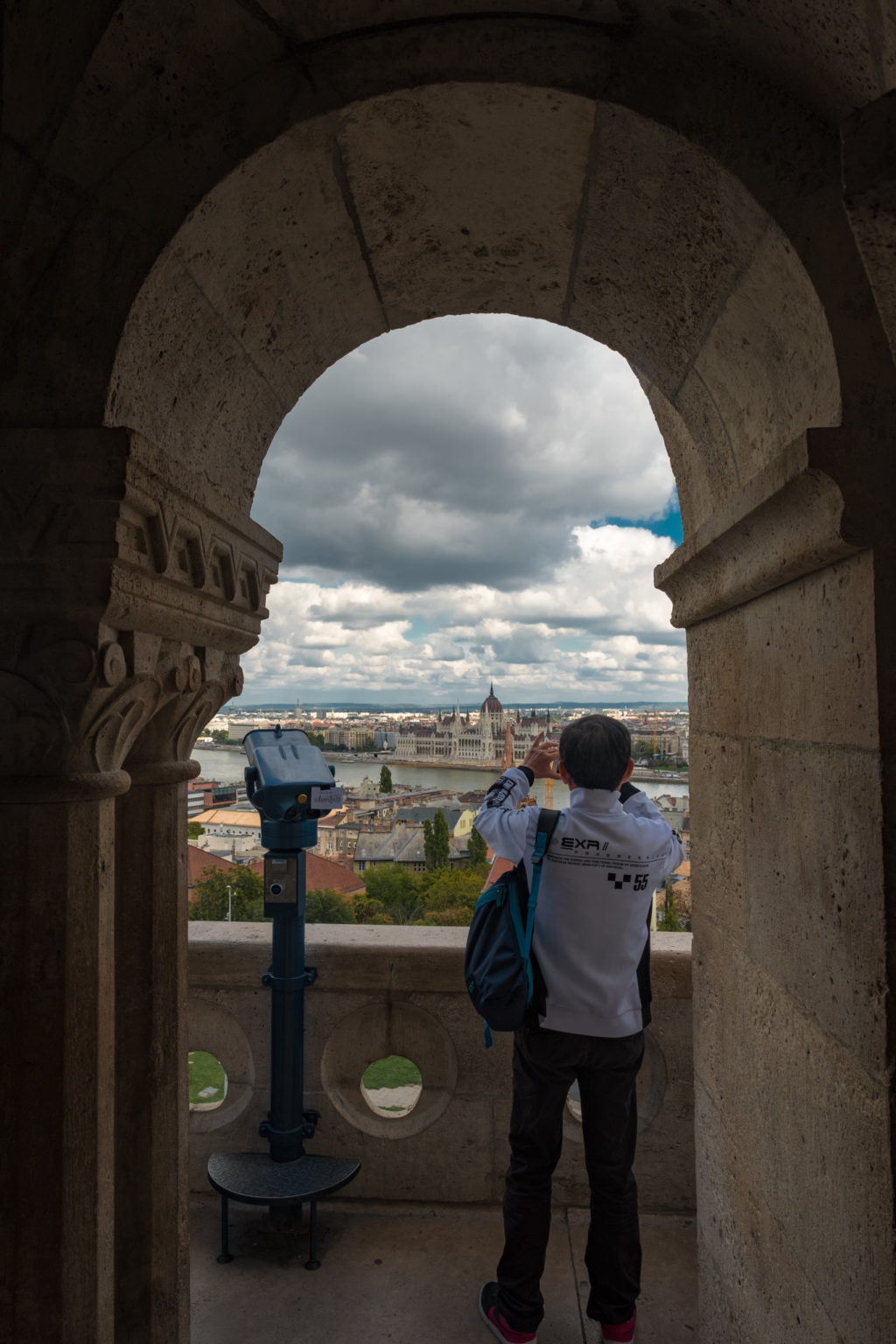 ourist takes photo of Budapest Parliament as seen through arch in Matthias Church, Hungary.