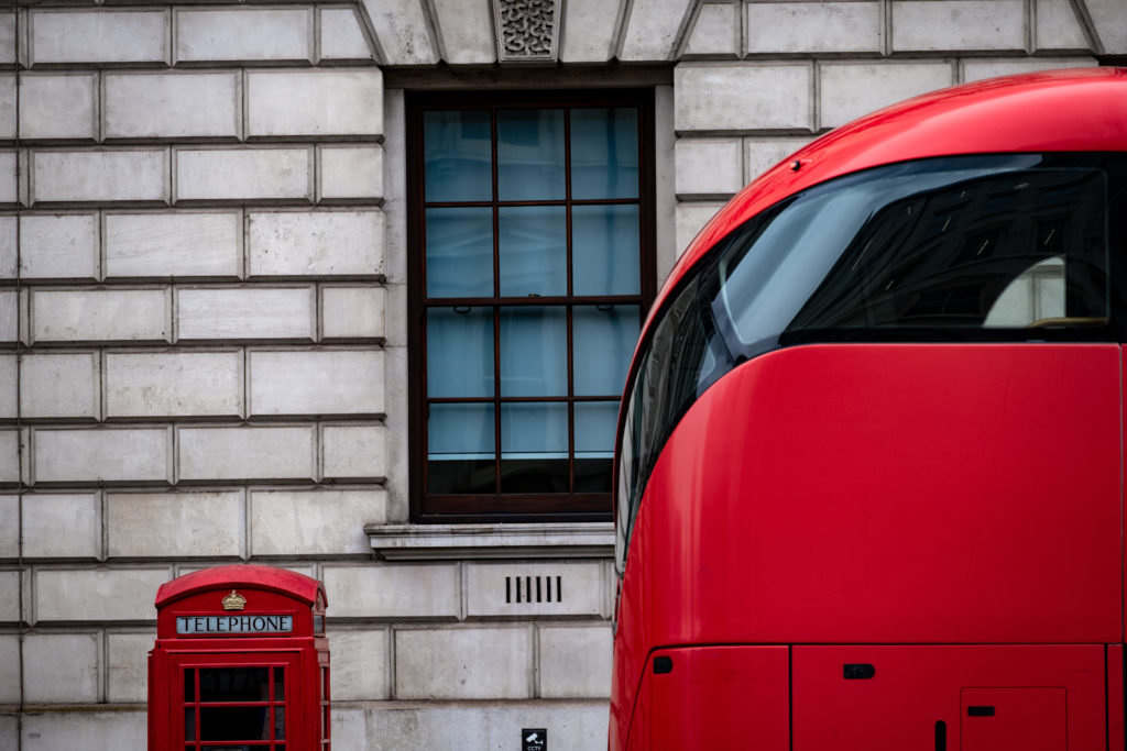 London bus and telephone box by a government building.