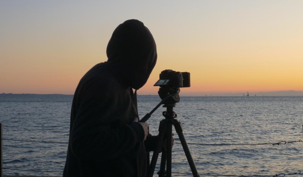 Man shooting video on coast during sunrise