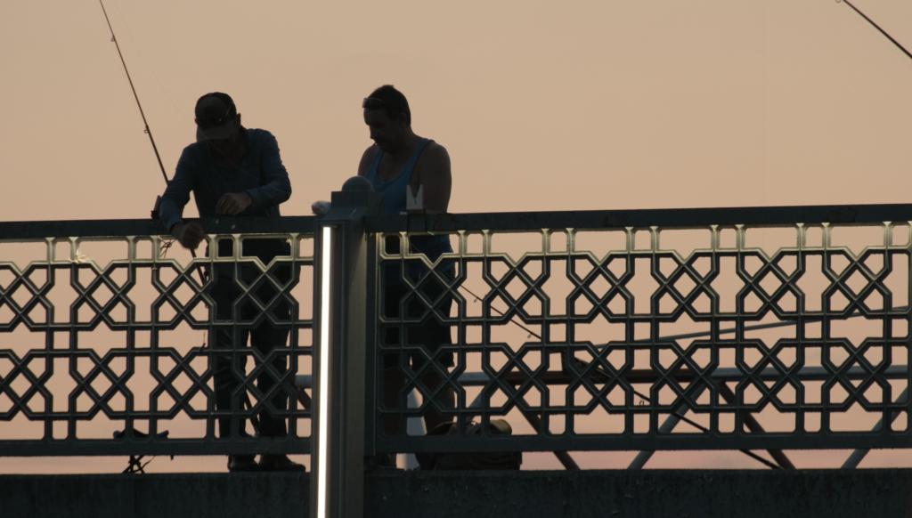 Fishermen on the Galata Bridge, Istanbul during sunset.