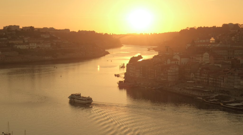 a boat sails into sunset in Porto, Portugal