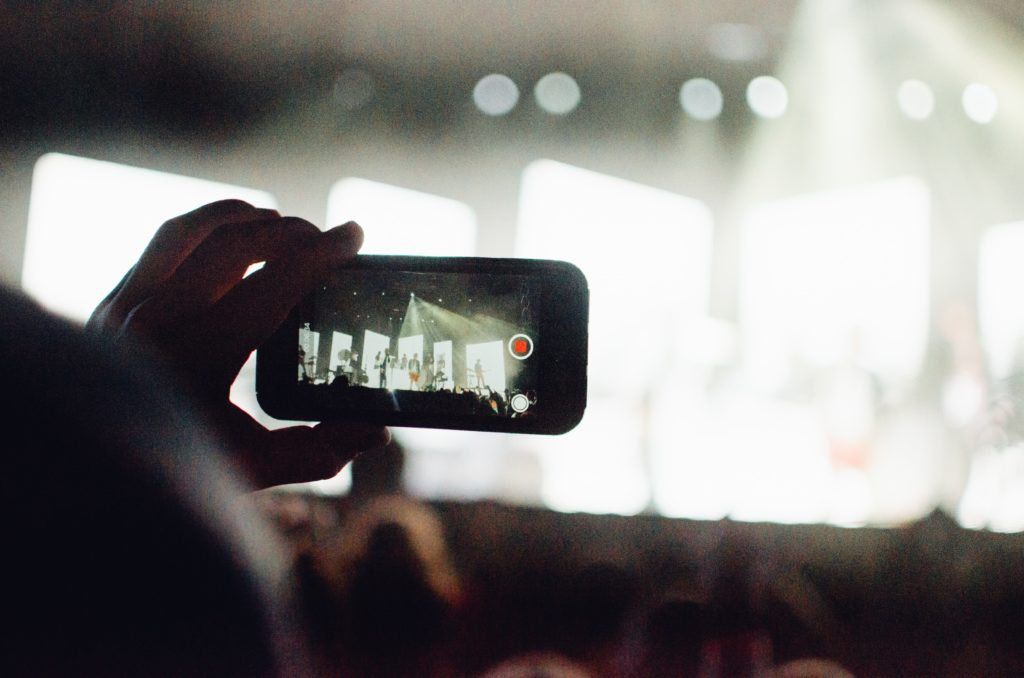 Man shooting video on phone at concert