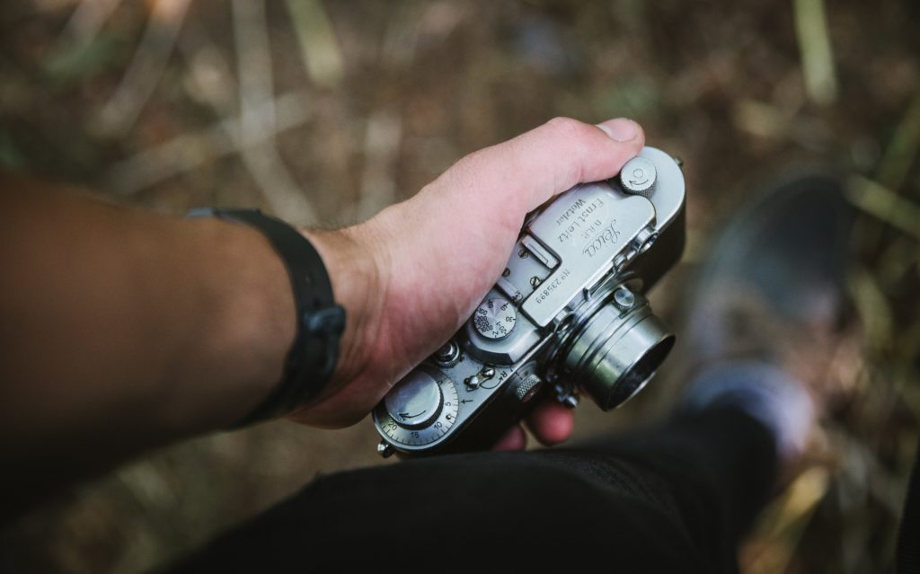 Hand holding a vintage Leica film camera.