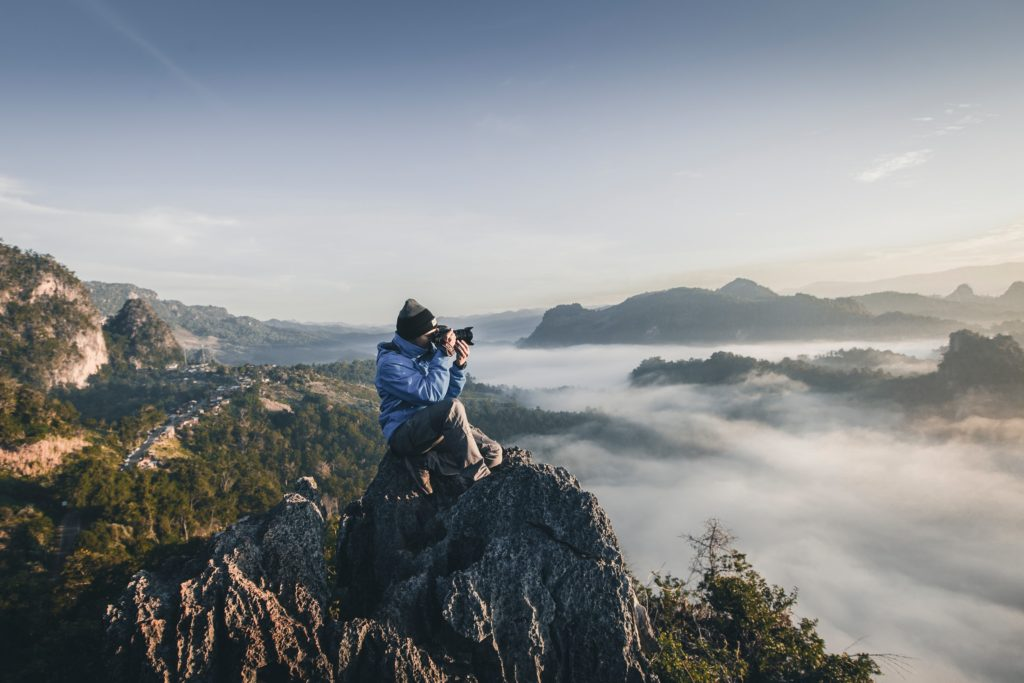 Man sitting atop a mountain taking a photograph