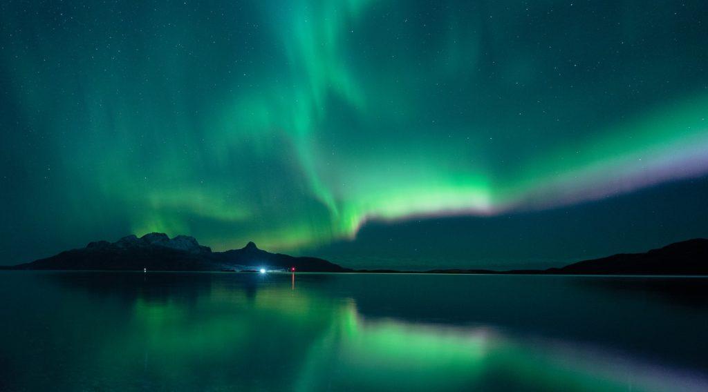 green aurora lights over lake