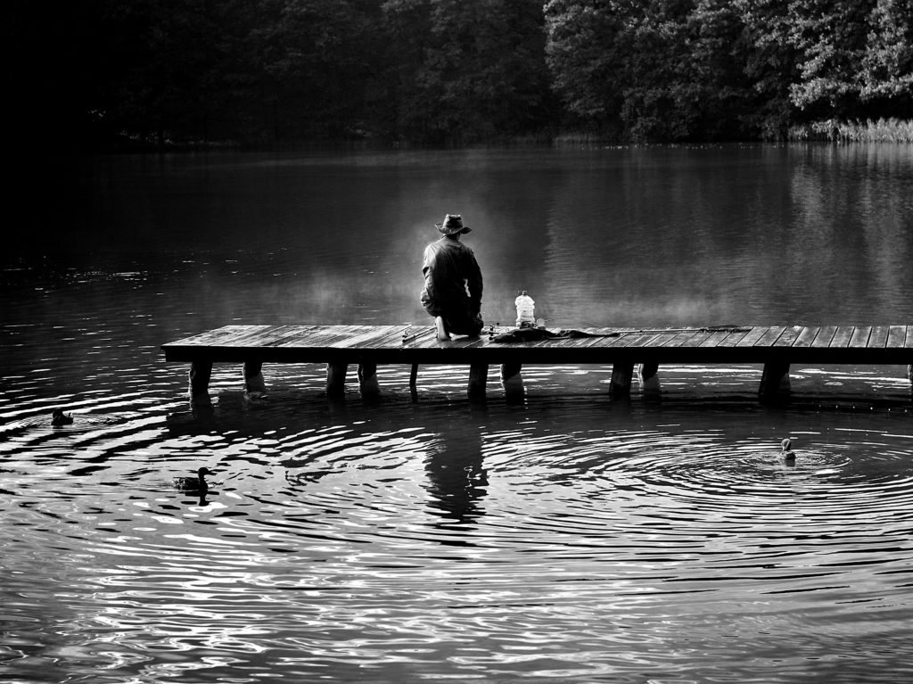 River with fisherman and jetty in black and white