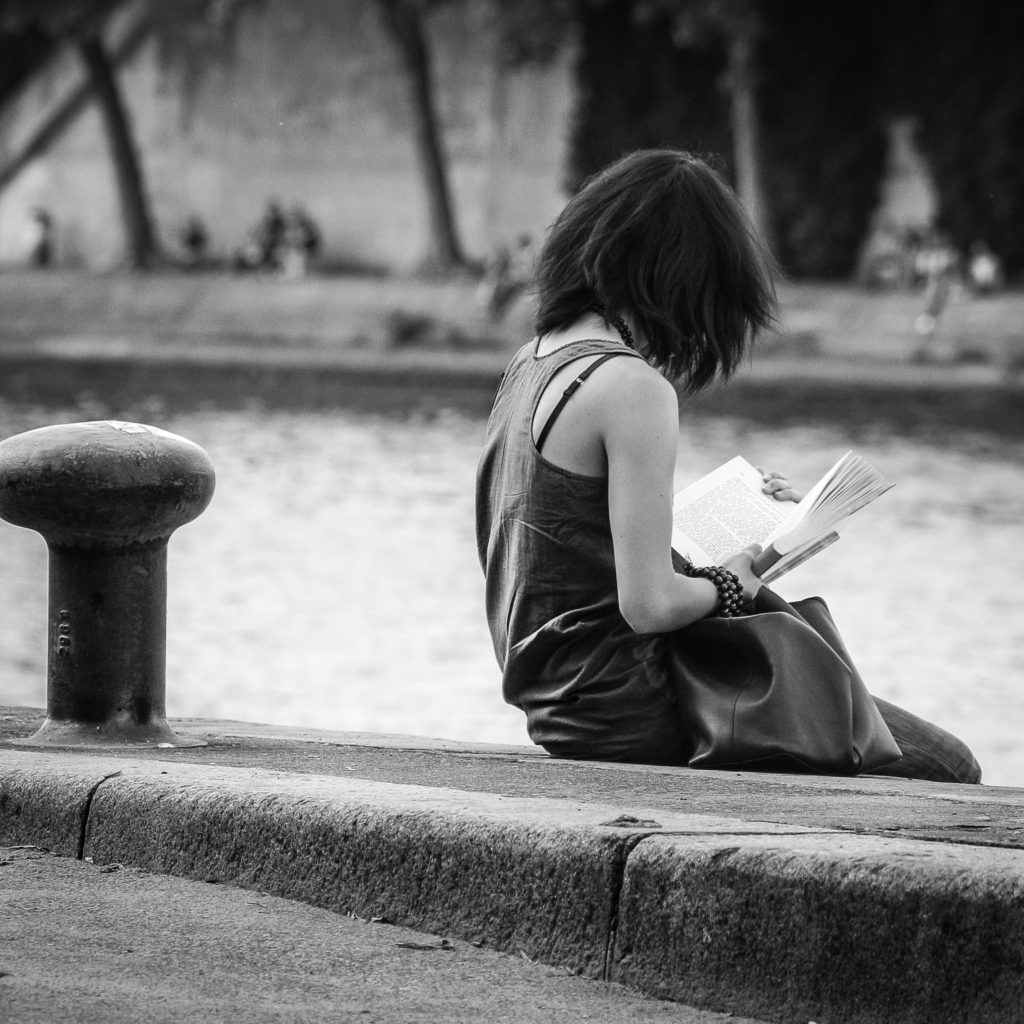 River with girl reading in black and white