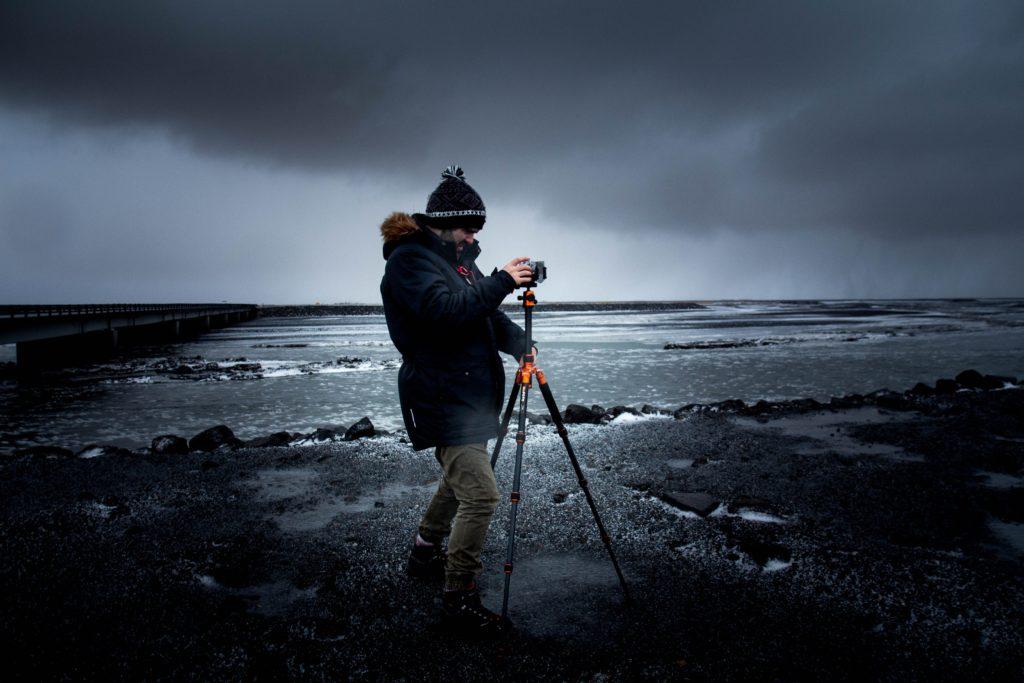Photographer with tripod on beach