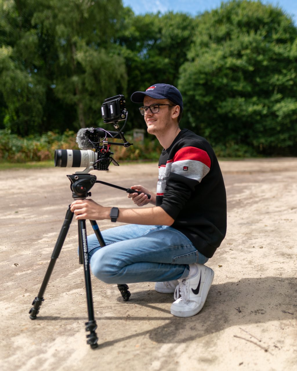 Man squats beside his camera and tripod