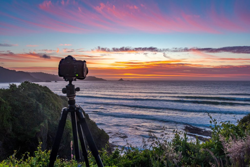 Camera on tripod looks out towards sunset