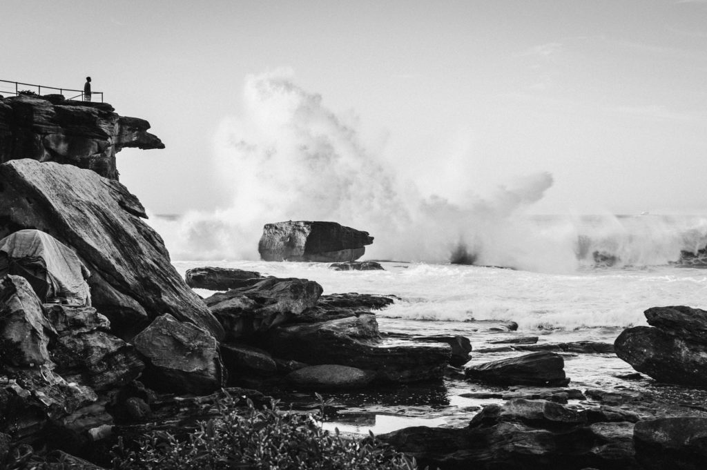 grayscale photo of manstanding at the edge of a cliff