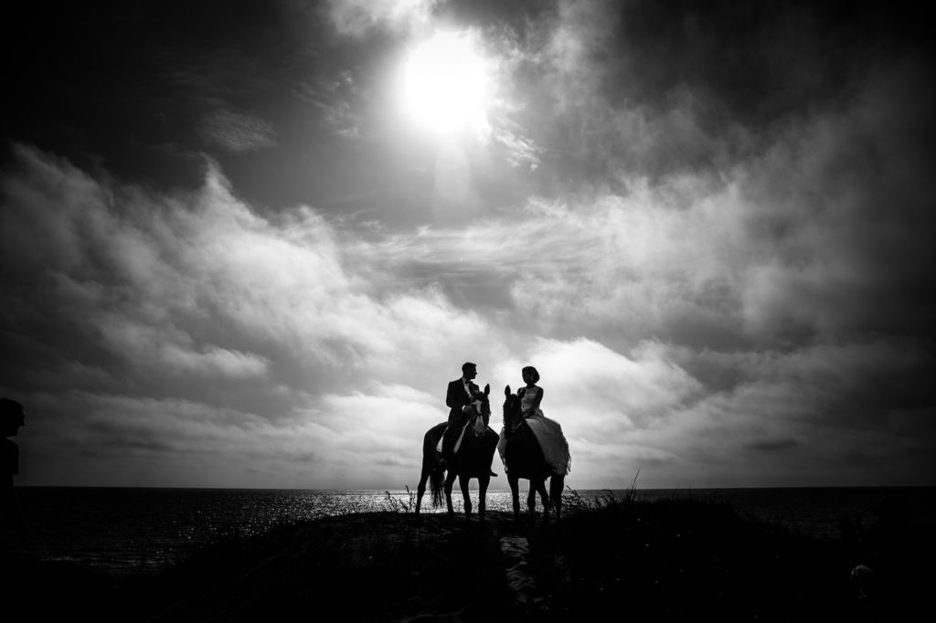 grayscale photography of couple riding on horse with body of