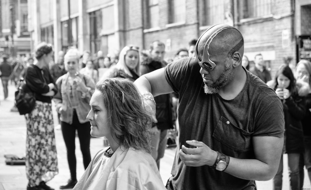 grayscale photography of man cutting hair of woman