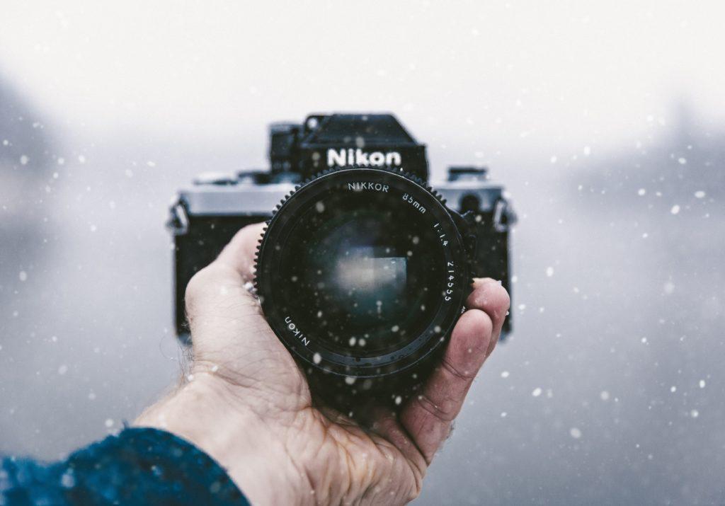 Man holding Nikon film camera in the snow