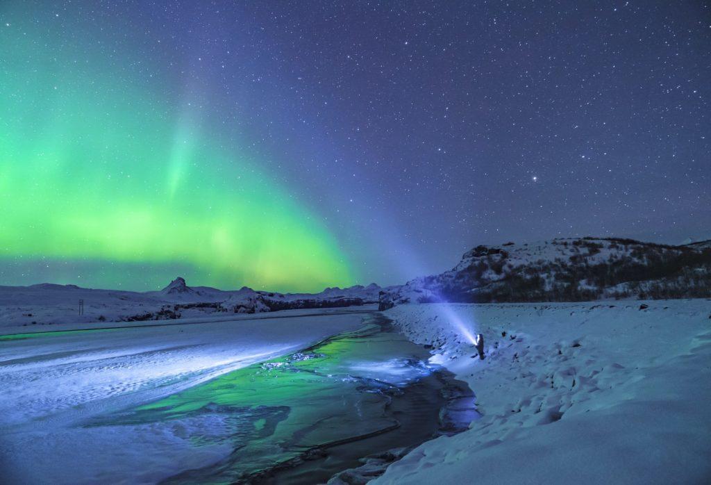 person standing under aurora lights