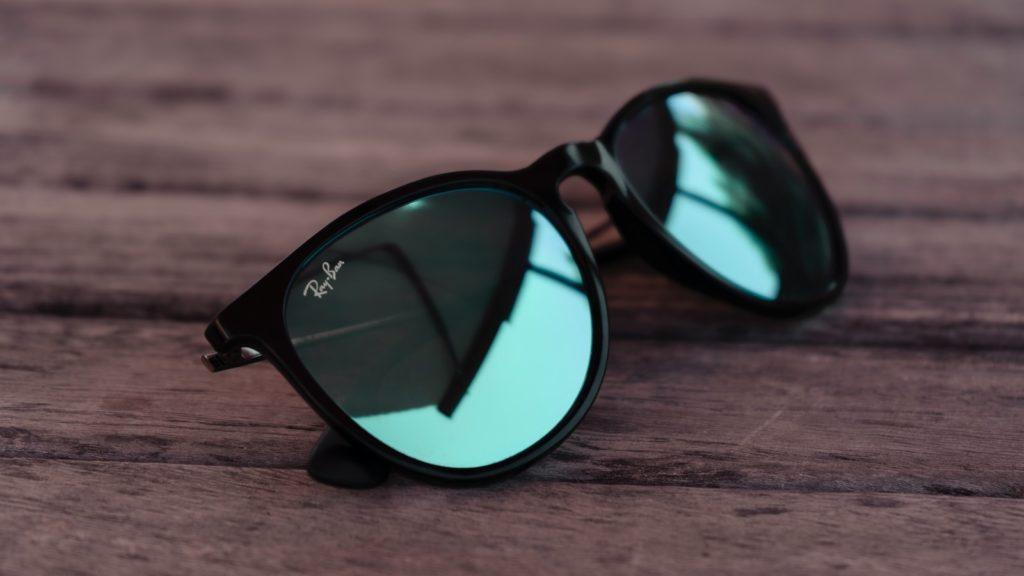 black framed sunglasses on brown wooden table