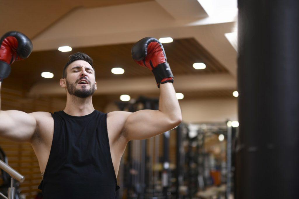 man in black tank top wearing red boxing gloves
