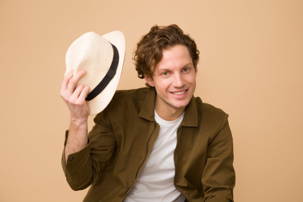 man wearing brown dress shirt holding white fedora hat