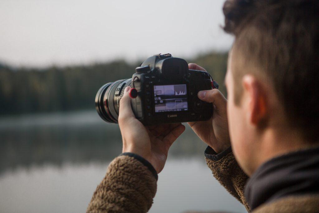 Man holding camera looking at live view