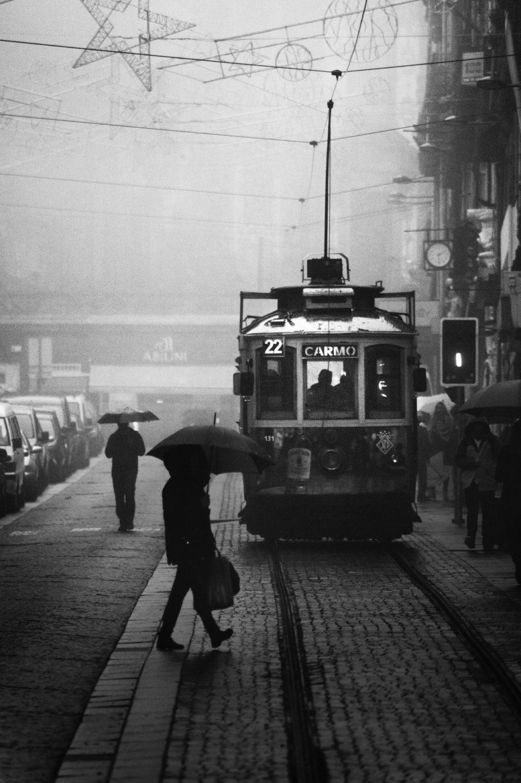 monochrome photo of people walking near tramway