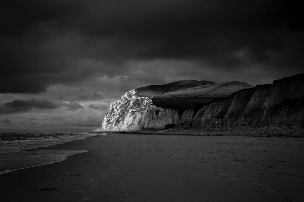 mountain near beach shore under dark cloudy sky